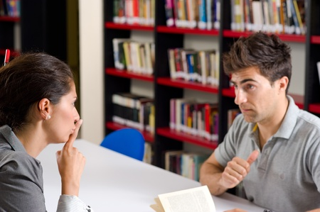 Woman asking her partner to be quiet in the library
