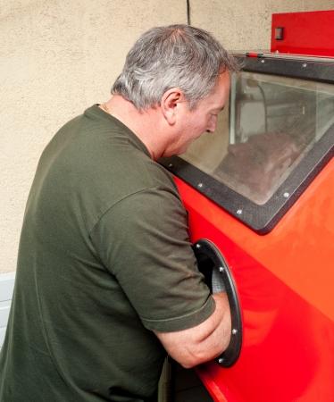 Operator working at a sandblasting machine