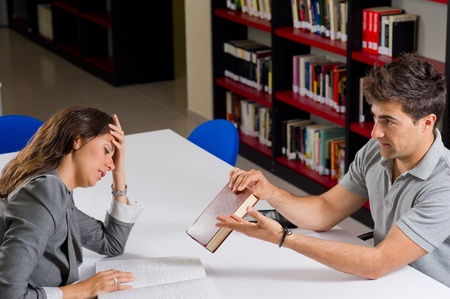 bother: Guy trying to encourage his girlfried to keep on with her studies Stock Photo