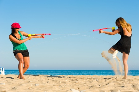 Girls with water pistols fooling around on the beach Stock Photo - 9680517
