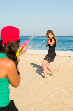 fooling: Girls with water pistols fooling around on the beach