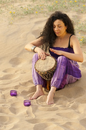 djembe drum: Woman outdoors enjoying the sunshine and playing her djembe