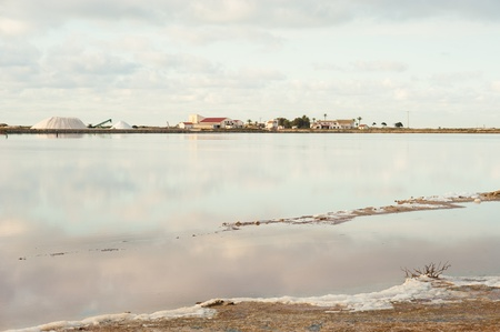 saltmine: Salt marsh with drying water and saltern factory in the background Stock Photo