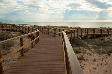 Stilted wooden footbridge leading to a Mediterranean beach Stock Photo - 9771903