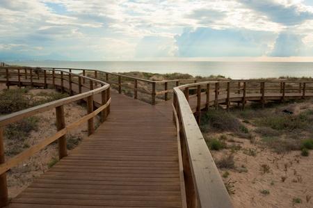 Stilted wooden footbridge leading to a Mediterranean beach Stock Photo - 9771903