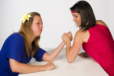 Blond and Hispanic girl competing by arm wrestling photo