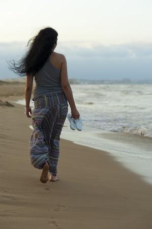 Hispanic woman enjoying a barefoot walk on the beach photo