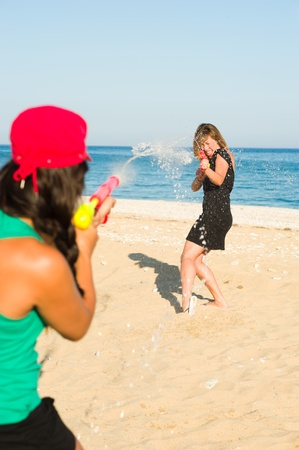 watergun: Girls with water pistols fooling around on the beach