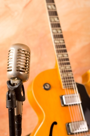 Vintage microphone and classic guitar waiting on stage