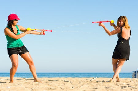 catfight: Girls with water pistols fooling around on the beach
