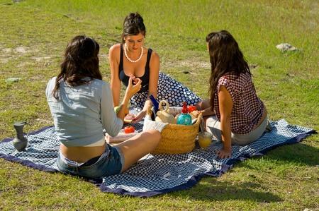 Girls  enjoying a classic  picnic  in a scenic setting photo