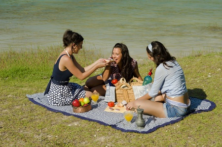 Girls  enjoying a classic  picnic  in a scenic setting photo