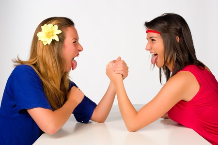 Blond and brunette girl at a crazy arm wrestling contest photo
