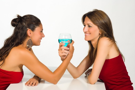 Girls toasting, one with alcohol, the other with water photo