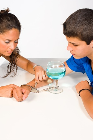 Woman unchaining a teenager from his alcohol addiction Stock Photo - 9976751