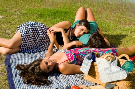 Girls resting after an ejoyable picnic outdoors photo