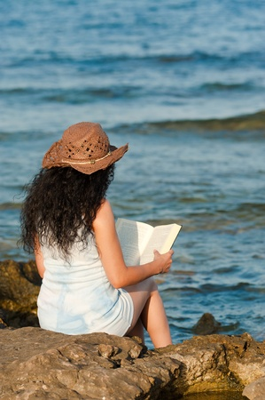Woman ejoying a book with her feet in the water photo