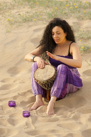 Woman outdoors enjoying the sunshine and playing her djembe photo