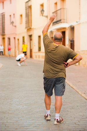 gesticulate: Traditional Spanish pelota player performing a serve