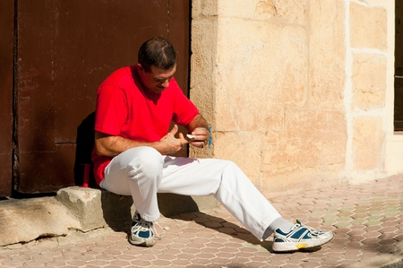 Traditional Spanish pelota player ritually wrapping his fingers in plaster protections Stock Photo - 11038969