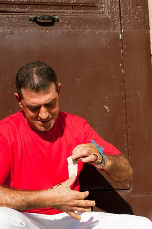 Traditional Spanish pelota player ritually wrapping his fingers in plaster protections Stock Photo - 11038968