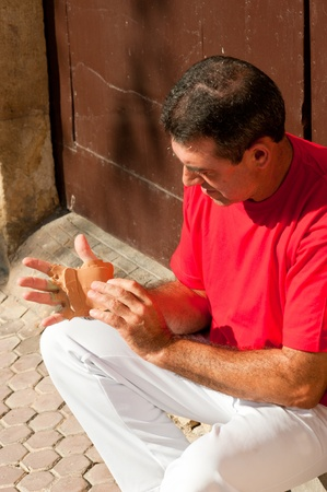 Traditional Spanish pelota player ritually wrapping his fingers in plaster protections Stock Photo - 11038967
