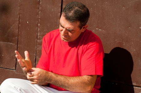 Traditional Spanish pelota player ritually wrapping his fingers in plaster protections Stock Photo - 11038970