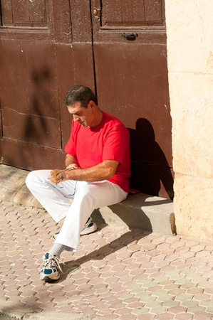 Traditional Spanish pelota player ritually wrapping his fingers in plaster protections Stock Photo - 11038972