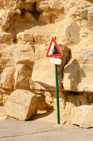 rockslide: Landslide warning sign surrounded by fallen rocks