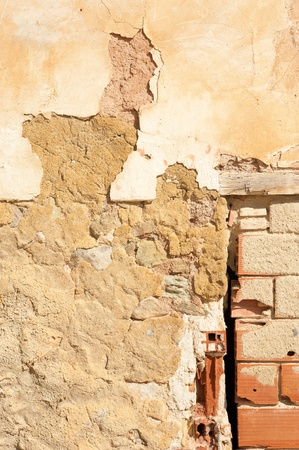 A weathered adobe and stone wall, a background photo