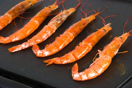 griddle: King prawns  being cooked on a griddle