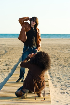 Woman taking photographs of a teenager on the beach photo