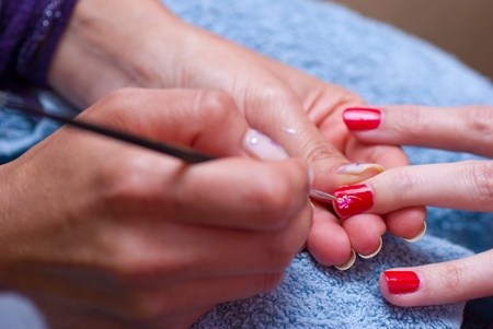 Beautician at work, decorating shiny red nails photo