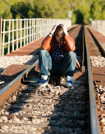 devastated: Depressive teenager sitting on a railway track, a concept Stock Photo