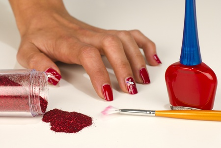 Hand with shiny red nails surrounded by nail art utensils Stock Photo