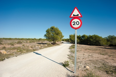 pot hole: Warning sign on a potholed unpaved country road Stock Photo