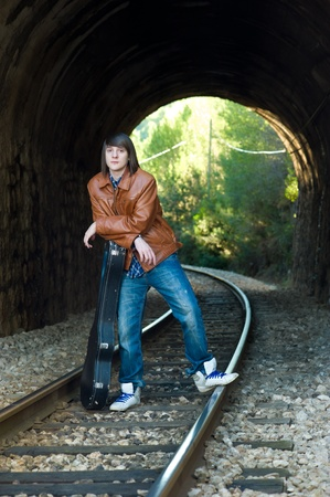 Cool guitarist portrayed inside a railway tunnel photo