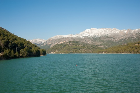 opalescent: Guadalest reservoir amidst winter with snowcaped mountains