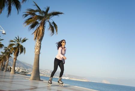 inline skating: Woman skating along a sunny Mediterranean beach