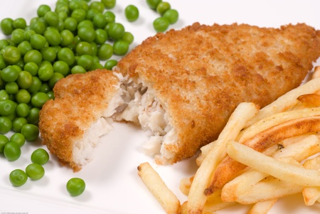 breaded: Classic English fish and chips served with peas Stock Photo