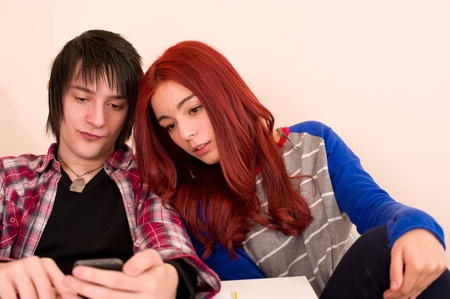 Student couple looking at something on a smarthphone photo