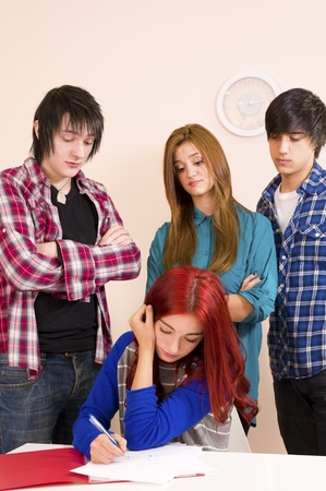 behaving: Three of her fellow students behaving in a hostile way Stock Photo