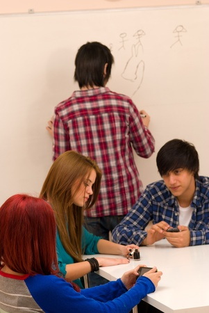 unmotivated: Distracted students passing time at boring scool Stock Photo
