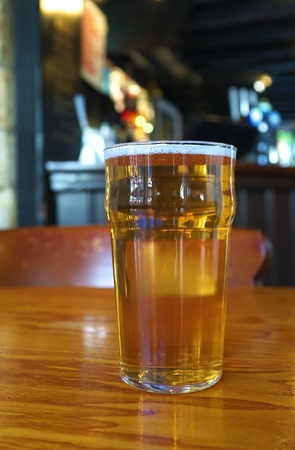 A pint of ale against the background of a traditional English pub