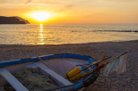ashore: Sunrise on a traditional fishing boat ashore Isleta del Moro beach