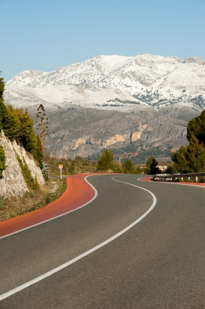 Scenic road bending amidst snowcaped mountains Stock Photo - 14054980