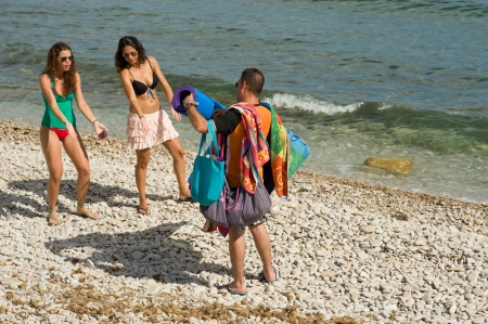Guy trying to be helpful carrying their beach stuff Stock Photo - 14121833