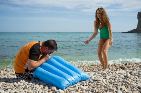 matress: Gentlemanlike guy inflating the air matress for the girl