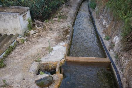 Een oude irrigatiekanaal het verstrekken van citrus velden met water Stockfoto