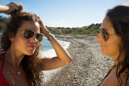 Girl mirroring in her friend´s glasses retouching her hair